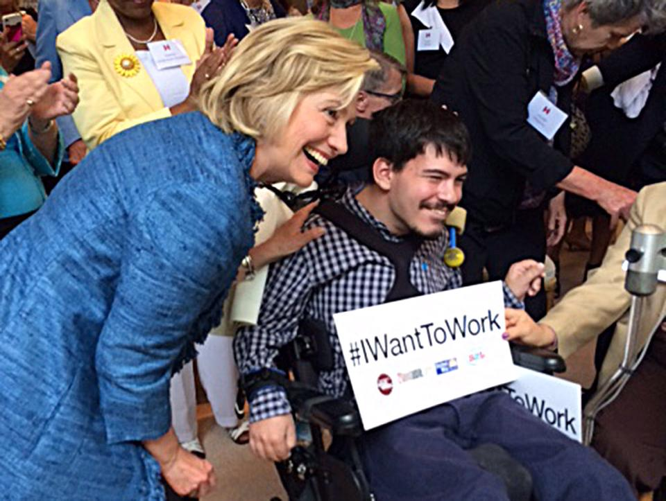 Hillary Clinton with a supporter in a wheelchair with a sign saying #IWantToWork
