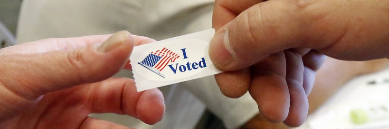 """Image of a male hand handing an """"I Voted"""" sticker to another hand"""
