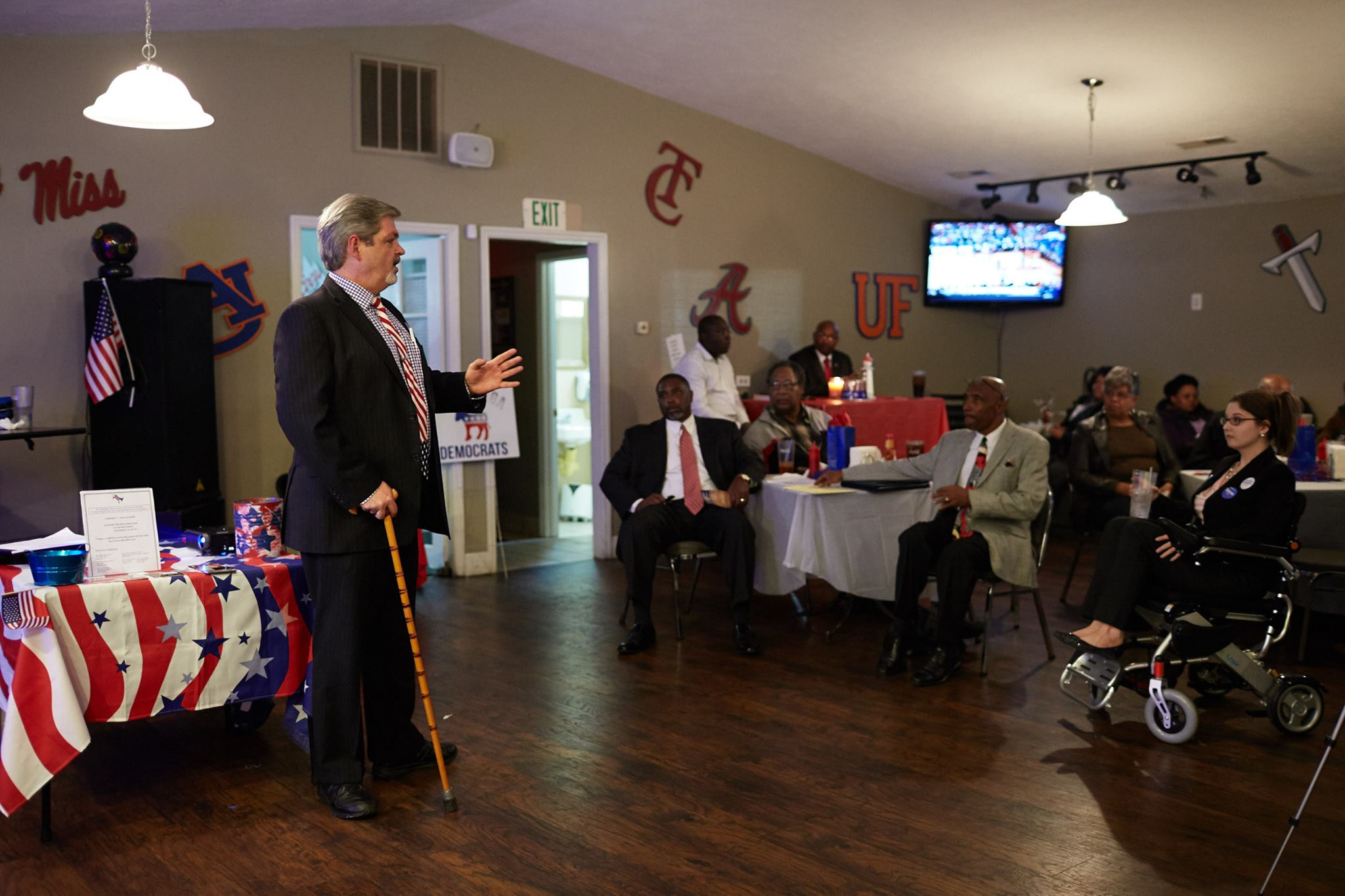 Ron Crumpton speaking at a campaign event. He is using a cane and there is a woman in a wheelchair in the audience.