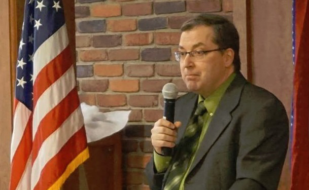 Joe DeMare standing and speaking while holding a microphone next to an American flag