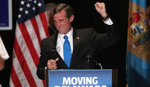 """John Carney speaking behind podium with sign saying """"moving Delaware forward"""""""