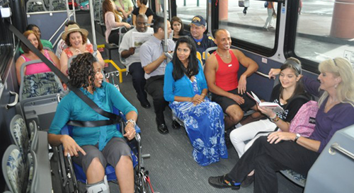 A young African American woman in a wheelchair is strapped in on a bus with a diverse group of people seated on the bus around her.