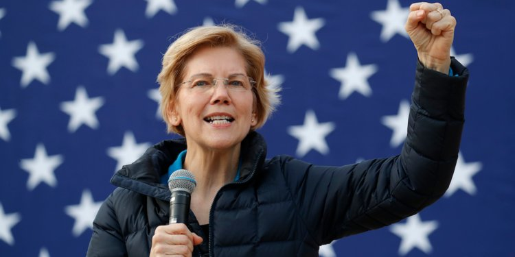 Warren speaks into a microphone with her arm outstretched in front of the U.S. flag