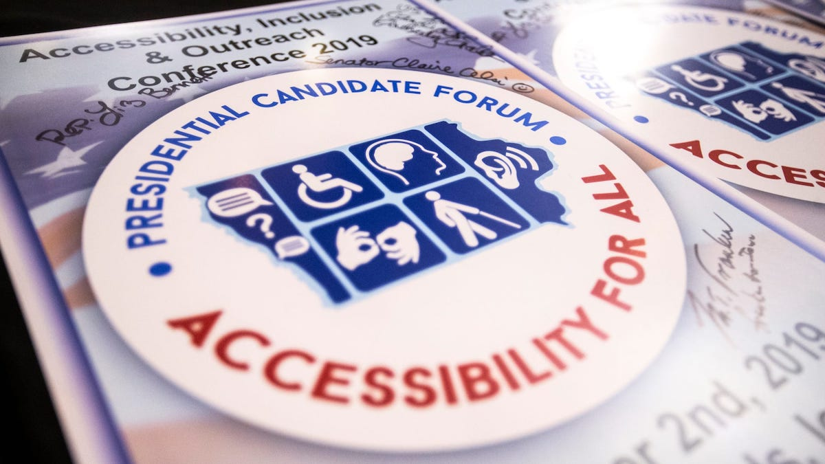 A poster with the logo for the Accessibility For All Presidential Candidate Forum signed by several candidates.