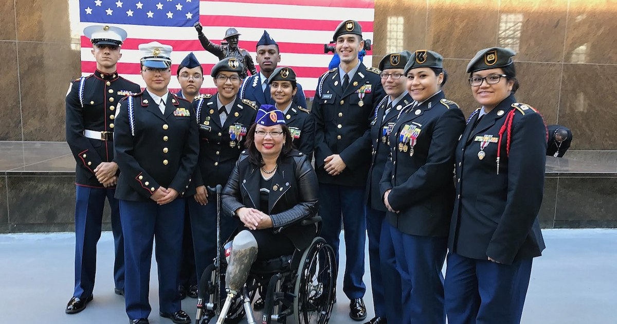 Tammy Duckworth with a group of other veterans smiling in front of an American Flag