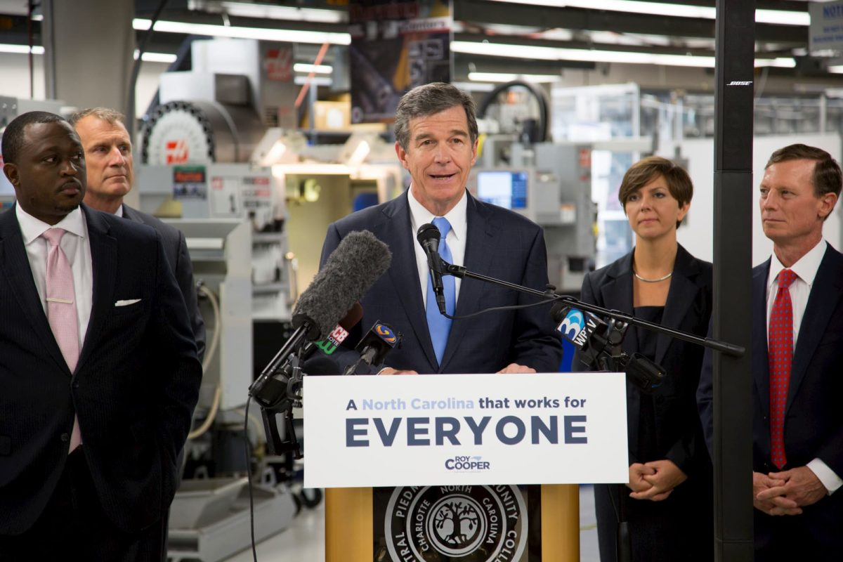 Roy Cooper stands behind a podium