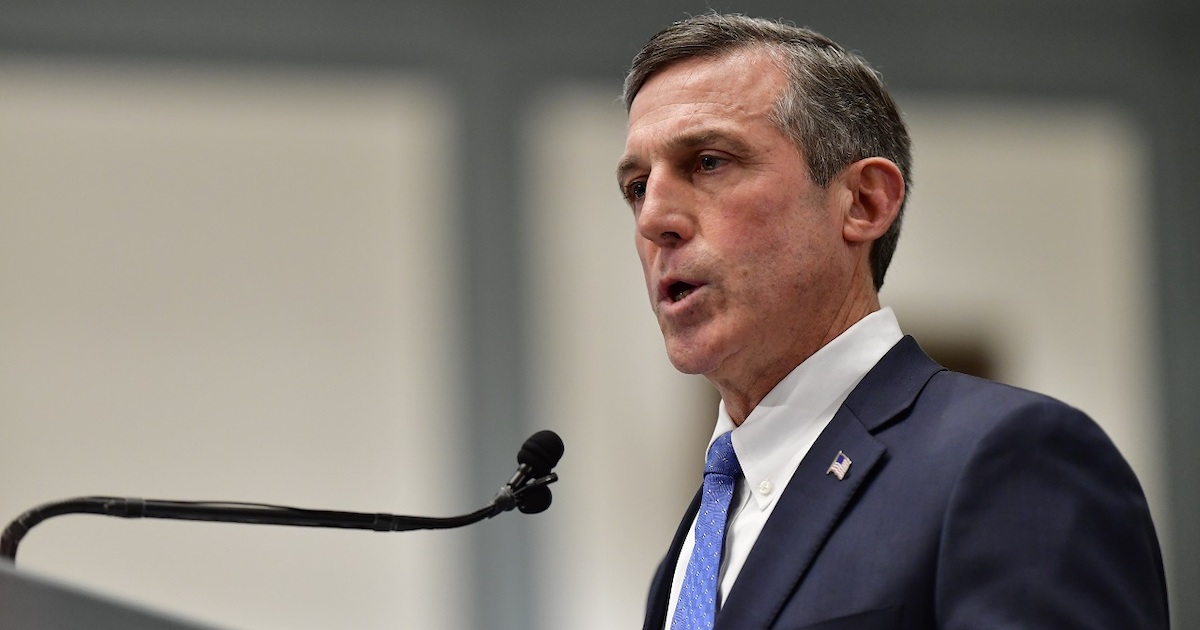 Governor John Carney speaking into a microphone wearing a suit and tie