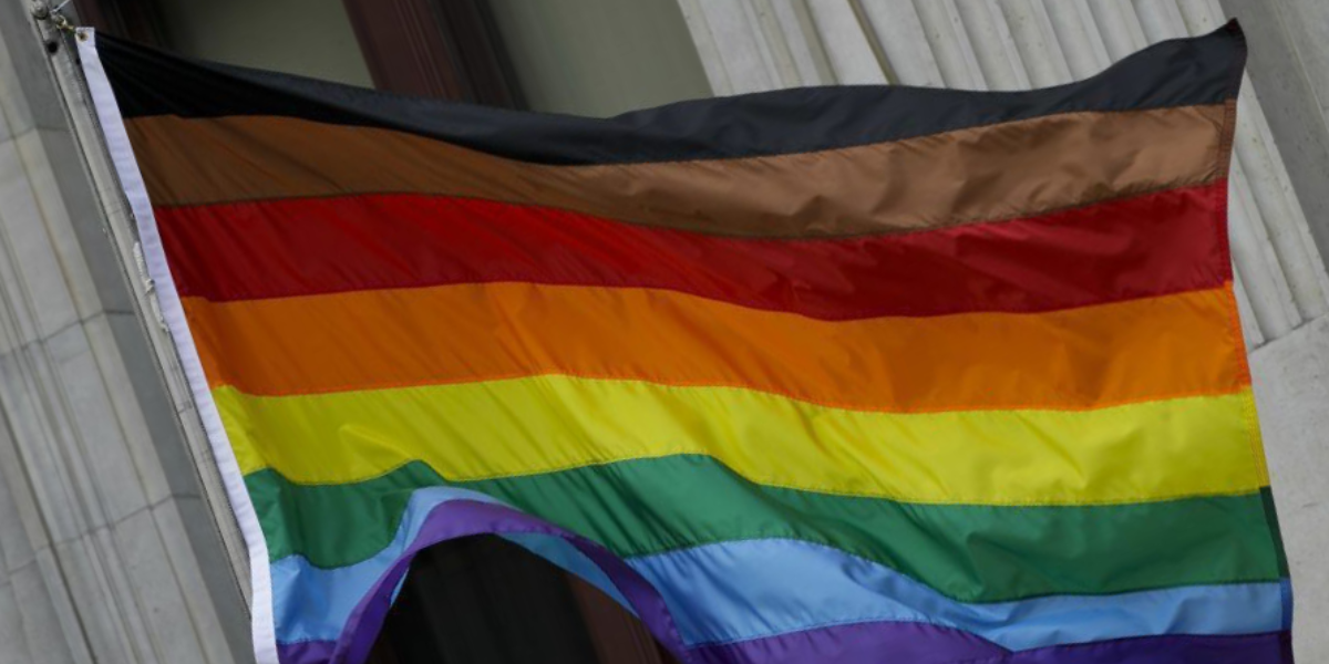 an LGBTQ+ Pride flag with black, brown, red, orange, yellow, green, blue and purple stripes
