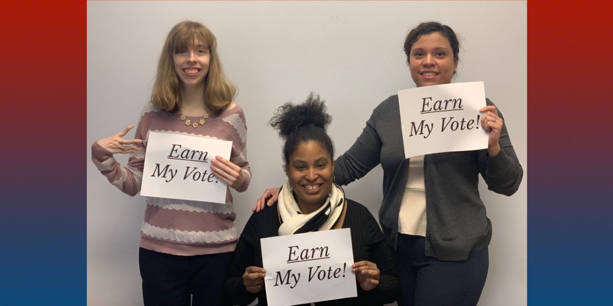 """Three RespectAbility team members holding up signs that say """"Earn My Vote""""."""
