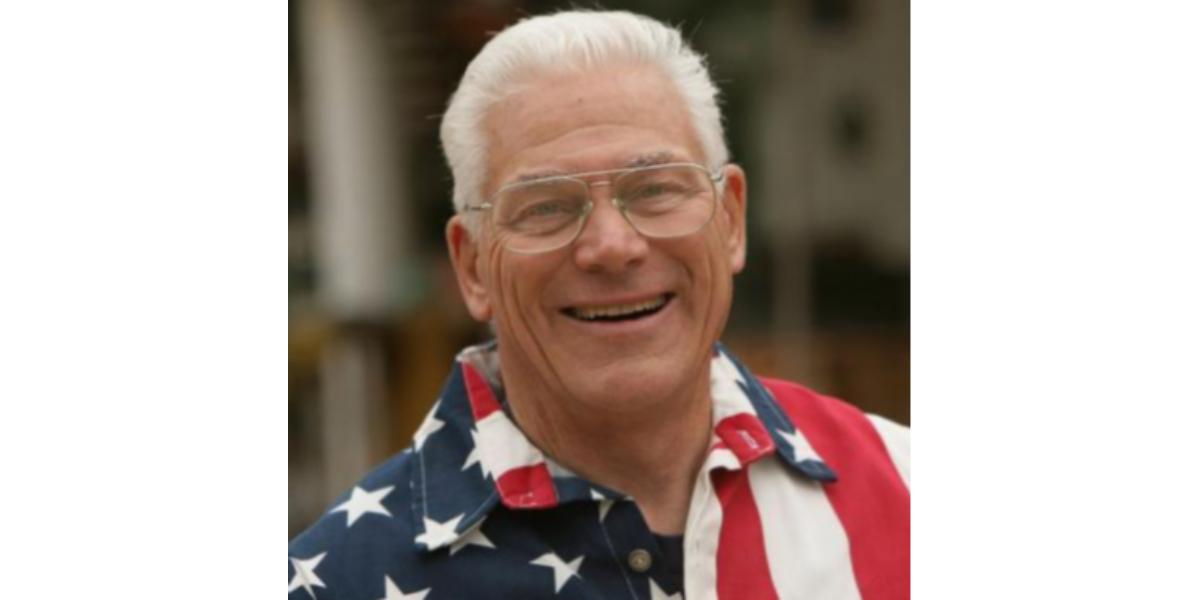 Robert C. Newman smiling headshot wearing an American flag polo shirt